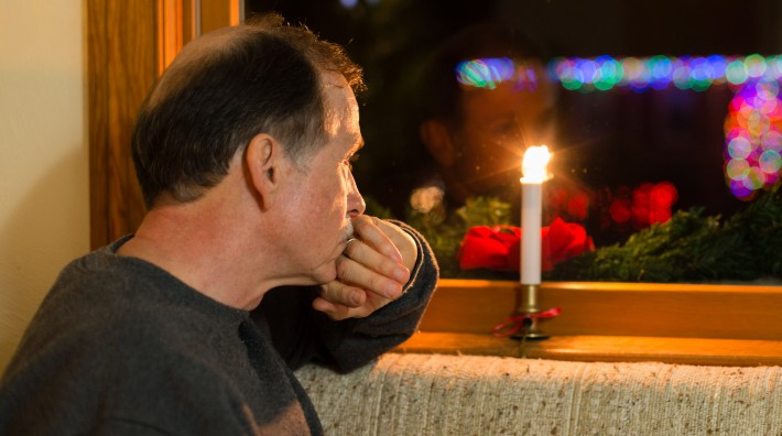 A depressed adult male looks out a window past Christmas decorations with Christmas lights in the background