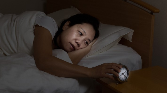 man who can't sleep looks at his sleeping wife in bed